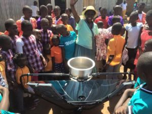 Mama Dolphine-showing SolSource-solar-cooker-to-children